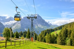 Yellow cable car in the Swiss Alps. Gondola going from Grindelwald to First in the Jungfrau area. Summer Alpine landscape with snowcapped mountains in the background. Transport tourists uphill.