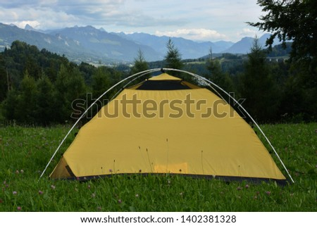Yellow camping tent built on a green grass near forest in wild nature of Switzerland. High peaks of mountains in in background, cloudy sky above. #1402381328