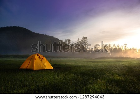 Yellow Camping Tent In The Middle of Open Field Near Forest During Sunrise at Summer Misty Morning. Concept of Outdoor Camping Adventure #1287294043