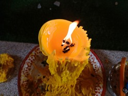 Yellow candle flame background lighting a large candle