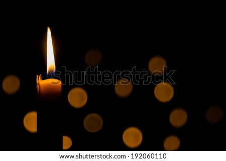 Yellow candle on the dark background and bokeh