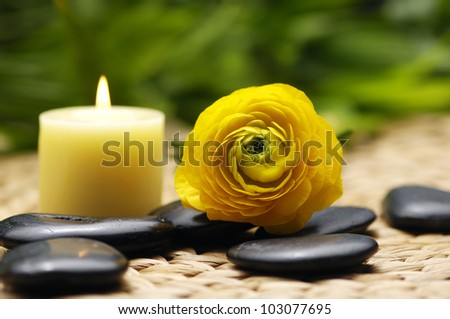 yellow candle with ranunculus and stones on mat