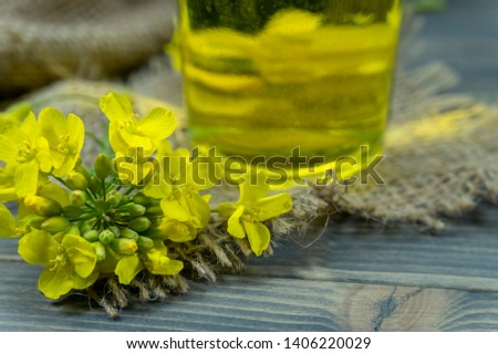 Yellow canola or rapeseed flowers with a small glass decanter of oil on a rustic table with hessian sack