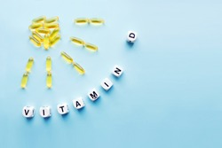Yellow capsules in the form of the sun with rays and word vitamin D from white cubes with letters on blue background. VITAMIN D word for healthy and medical concept. Sunshine vitamin health benefits