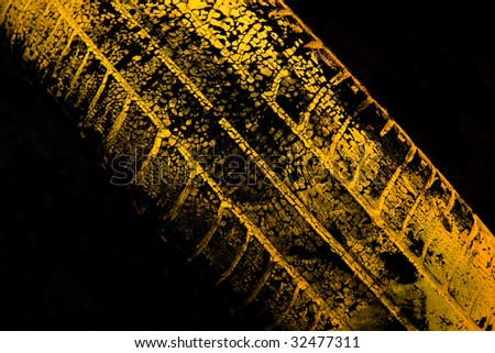 Yellow car tire print on black background