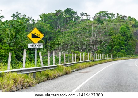 Yellow Caution Ascent 1km uphill 6% incline street traffic arrow symbol sign on dual carriageway highway through scenic mountain countryside landscape where cars/vehicles drive on left side of roads #1416627380