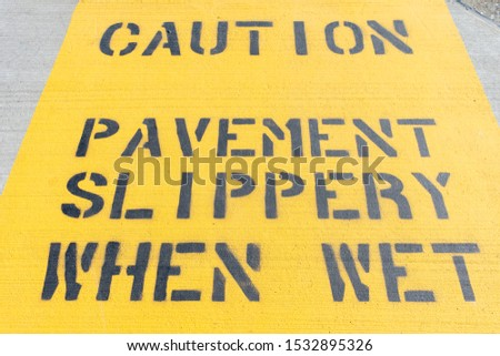 Yellow Caution Pavement Slippery When Wet Sign on the Ground