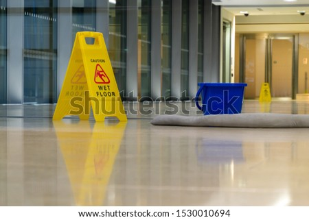 Yellow caution sign showing warning of slippery wet floor.