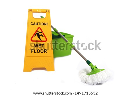 Yellow Caution slippery wet floor sign with mopp and bucket in the background - Safety sign cleaning service - isolated on white background Stock foto ©