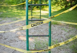 Yellow caution tape at the children old play structure during  covid19 pandemic quarantine in a sunny summer day with sand and grass in the background
