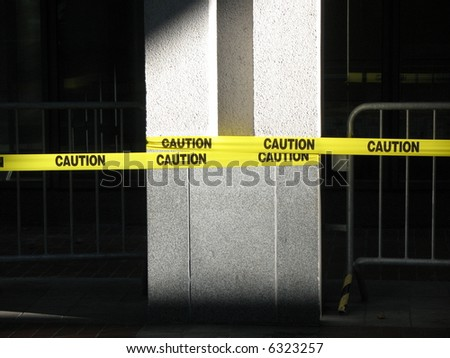 Yellow caution tape wrapped around a concrete pillar