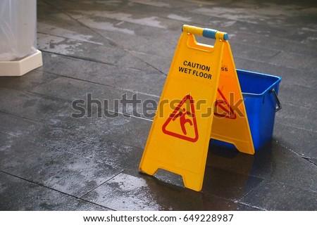 Yellow Caution wet floor sign on wet floor with blue bucket  #649228987