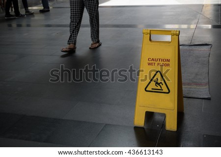 Yellow caution Wet Floor sign with blur background leg of people is walking. #436613143