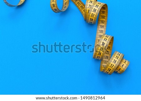 Yellow centimeter tape on a blue background. Minimalistic background. Selective focus. Free space for text.