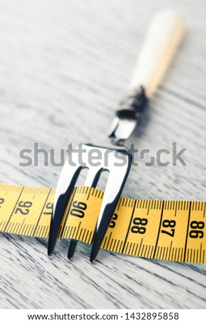 Yellow centimeter wrapped dessert fork on an old wooden table with the number 90. The concept of restriction in food for a slim figure with parameters 36 24 36 or 90 60 90