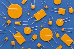 Yellow ceramic and polyester film capacitors of a square and round shape on a blue background close-up. Top view