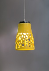 Yellow ceramic chandelier. The original pendant lamp of yellow color in an interesting form with openings.