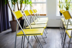 Yellow chairs in a room. Interior with row of yellow chairs. Emprty conference hall. Cancelled event. Quarantine social distansing