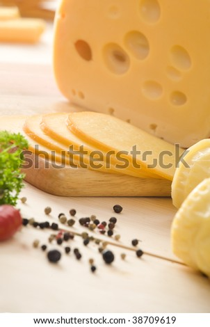 Yellow cheese with slices, some peppers, parsley and spices. All on wooden table.