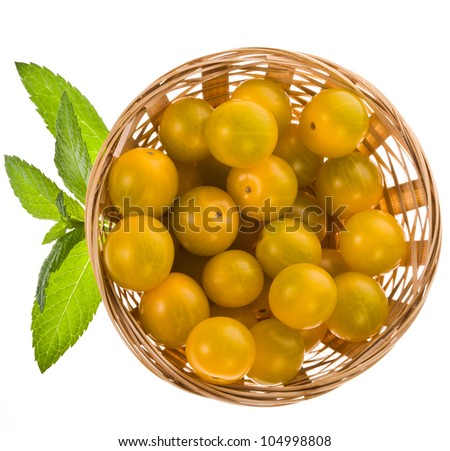 yellow cherry tomatoes in a wicker basket with green leaves isolated on white background