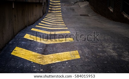 Yellow chevrons painted on road in urban alley way #584015953