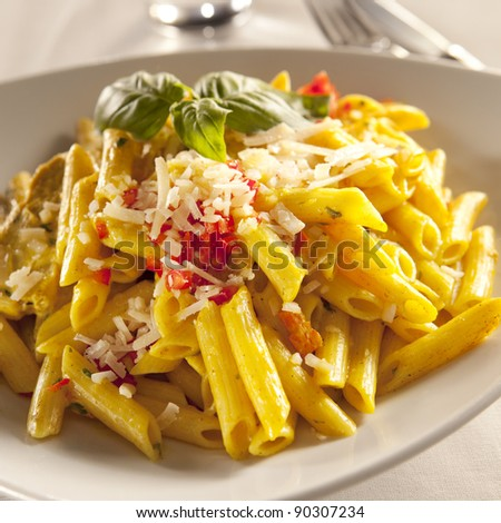 Yellow chicken pasta with parmesan cheese and chili pyree