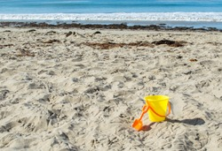 yellow child's sand pail with orange shovel in the sand at an ocean beach on a sunny summer day