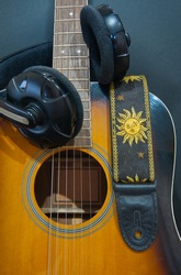 yellow classic six-string guitar with a leather strap depicting the sun and a headphone. musical instruments and accessories. guitar production