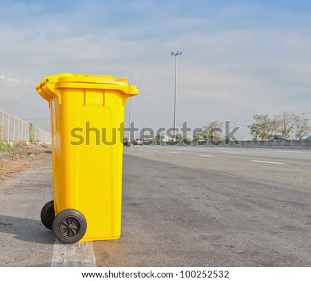 Yellow clean garbage bin on highway