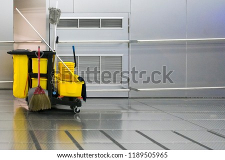 Yellow cleaning trolley park in walkway on stainless wall background.