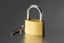 Yellow closed padlock and key to it on a gray background.