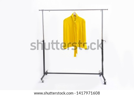 yellow clothes are hanging on Clothes Hanger,