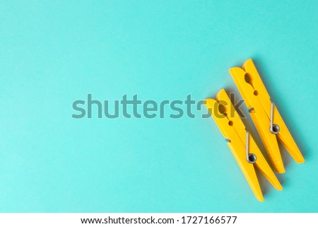 Photo of  Yellow clothespins on a blue background with copyspace