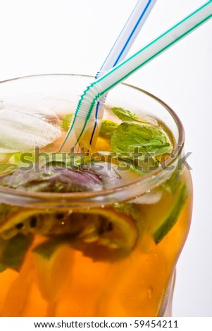yellow cocktail with mint, ice, lime and passion fruit served in stylish glass