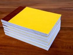 Yellow color bill books or receipt books on a wooden surface, close up shot