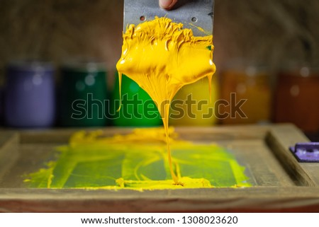 yellow color dripping from hand screen printing during printing tee shirt in tee shirt factory.