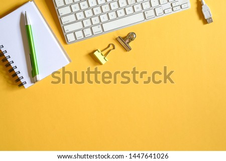 Yellow color office desk, top view with keyboard, cable, pen, memo pad and clips with copy space #1447641026