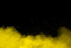 Yellow color powder explosion on black background.