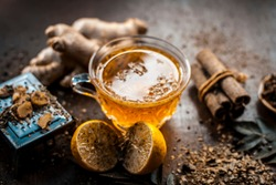 Yellow colored lemon ginger tea with all its ingredients in dark Gothic colors.Lemon ginger tea improves the immune system, reduce fever,improve cognition,regulate blood sugar,etc.