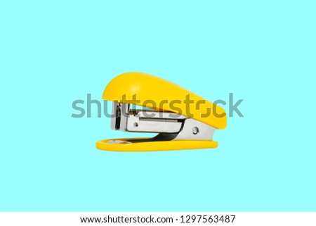 Yellow-colored stapler closeup on a blue background