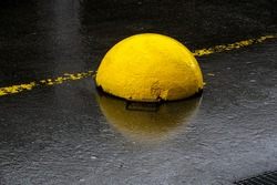 Yellow concrete boundary hemisphere with yellow lane markings behind on the wet black asphalt of a supermarket car park.