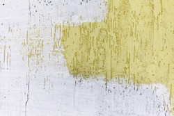 Yellow concrete wall and something blurred out with white paint. Grunge street background