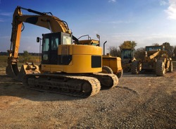 Yellow construction and excavation equipment including backhoe bulldozer and grader