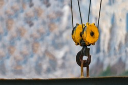 yellow construction crane hook with some industrial buildings on the background,for lifting hoist.selective focus,vintage color