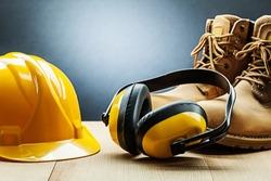 yellow construction earphones helmet and working boots