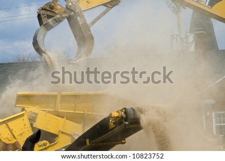 Yellow construction equipment loading rubble into a dump truck  (a lot of construction dust showing)