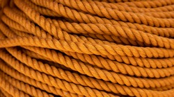 Yellow cord background, close-up photo. Braided rope texture. Ship or rock climbing tackle. Natural material woven cordage. Simple rope bulk concept. Alpine mountaineering equipment. Safety orang rope