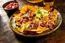 Yellow corn nacho chips garnished with ground beef, guacamole, melted cheese, peppers and cilantro leaves in plate on wooden table