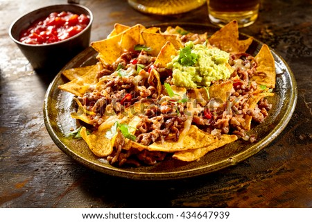 Yellow corn nacho chips garnished with ground beef, guacamole, melted cheese, peppers and cilantro leaves in plate on wooden table #434647939