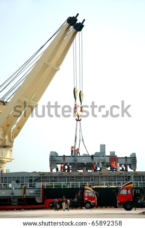 yellow crane and construction worker on ships freight